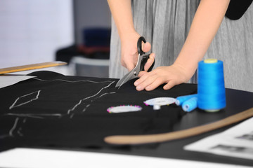 Young seamstress cutting out suit detail in atelier