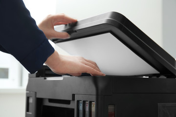 Woman making copy of document in office, closeup