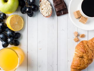 Breakfast on a White Table Coffee Croissant Orange juice Grapes Apple Chocolate Copy Space for Text
