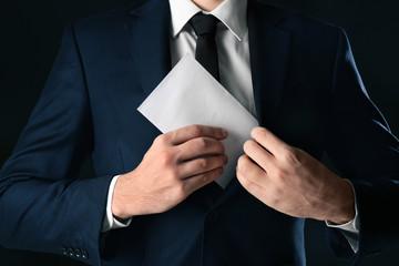 Businessman putting envelope with bribe in pocket on black background