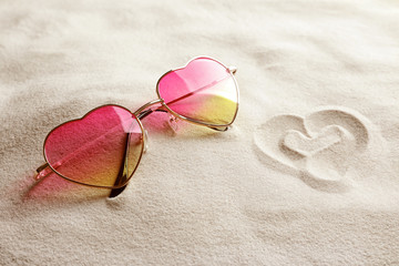 Glasses in shape of heart on white sand