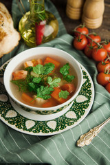 Vegetable soup, Uzbek shurpa soup on a green napkin, with cherry tomatoes and bread pita