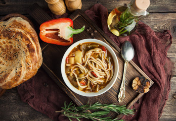 Asian Lagman soup with noodles and meat on a wooden board with olive oil and bread pita