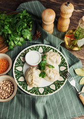 Asian Uzbek manti dish with sour cream on a green napkin with chickpeas and spices