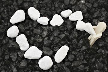 Hölzernes Männchen schließt ein weißes Kieselsteinherz - Symbol des Arbeitens an der Liebe