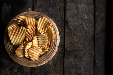 Served fresh baked potatoes chips on wooden background with blank space