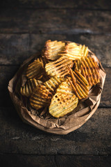 Fresh baked potatoes chips served on the wooden table,selective focus