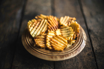 Fresh fried potatoes chips served in the wooden bowl,selective focus