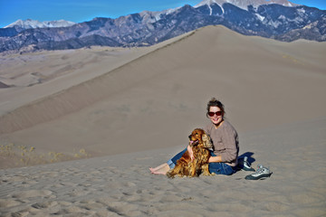 Young woman and her dog in Great Sand Dunes, Colorado