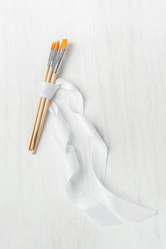 Various Typed of Paint Brushes Tied with Silk Ribbon on White Wood Table. Copy Space for Artwork Lettering Calligraphy Text Inspirational Quote. Creativity Arts Business Product Branding Promotion