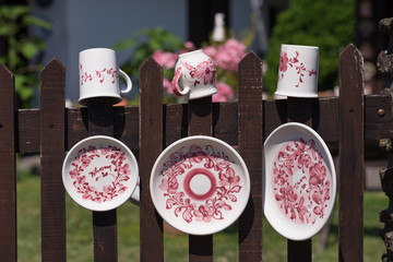 Colorful traditional hand-made porcelain dishes hanged on the fence
