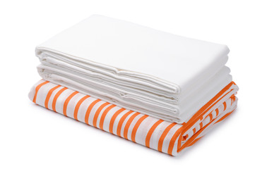 Stack of folded white and color bedding sheets