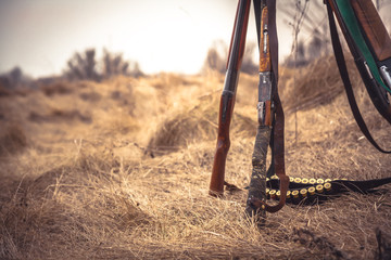 Door stickers Hunting Hunting scene in wild west with hunting shotguns and ammunition belt on dry grass in rural field during hunting season as hunting background with copy space