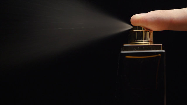 Cinemagraph - Close up of a spray bottle drops on black background. Male perfume bottle on a dark background. close up of a spray bottle drops on black background