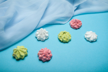 Multi Colored sweet meringue traditional form isolated on blue background.