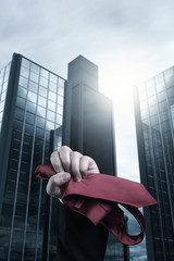 business fist raising up with red tie in front of skyscraper and in rainy weather