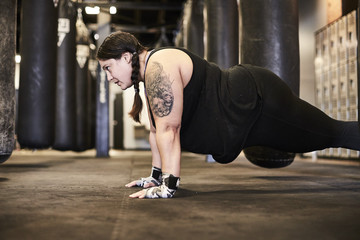A woman working out at a boxing gym by holding a plank while wearing her wrist wraps.