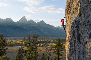 Female climber climbing in Teton Range during autumn, Wyoming, USA