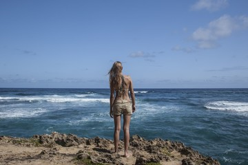 Young woman standing on coastline and looking at ocean, Kauai, Hawaii, USA