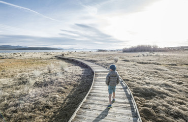 Rear view of boy walking alone on boardwalk across grass in front of Mono Lake, California, USA
