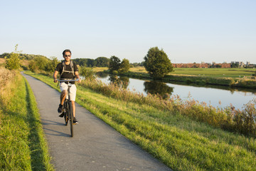 Young man wearing shorts and black shirt riding bike at sunset, Groningen, Netherlands