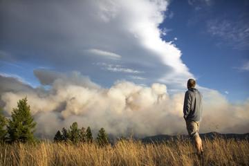Man watching Lolo Peak Fire blow up in heavy winds from top of Blue Mountain near Missoula, Montana, USA