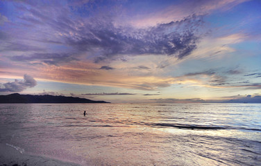 Silhouette of person swimming in Bali Sea at sunset, Gili Islands, Indonesia