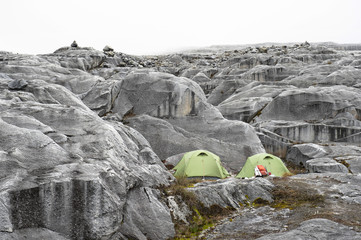 Two tents at campsite on moraine during climb to Pulpito del Diablo in Sierra Nevada del Cocuy, Colombia