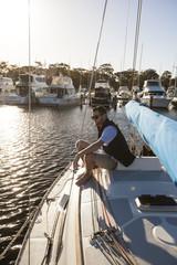 Sailor sitting on foredeck of sailboat, Perth, Western Australia, Australia