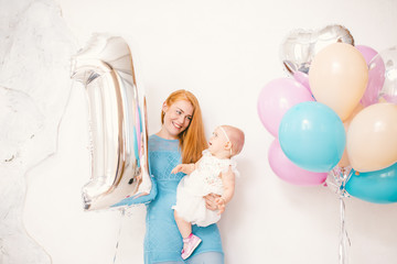 young red-haired mother holding a baby girl one year in a dress on a white background at home. The concept of a children's holiday is decorated with inflatable airy multi-colored balls