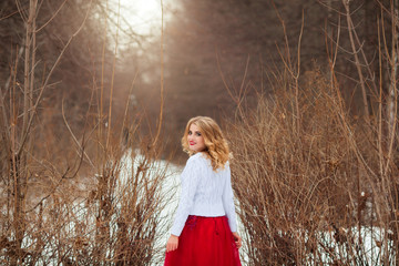 beautiful young blonde girl in white sweater and red dress with makeup and hairdress outdoors in snowy forest