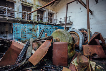 Ruined abandoned hydroelectric power plant. Rusty generator at machinery. Demolished roof. Gagra, Abkhazia