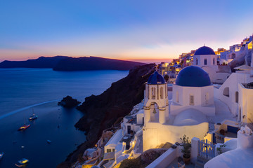 Wall Murals Lavender Cityscape of Oia, traditional greek village with blue domes of churches, Santorini island, Greece at dusk.