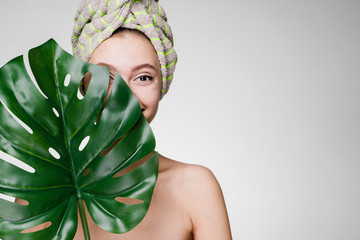 cute young girl with a towel on her head holds a green leaf, enjoying spa treatments