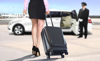 Women with suitcase at the airport leaving with white limo