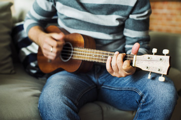 Caucasian man practicing ukulele