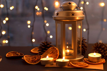 Christmas composition with lantern, candle, bumps, dried oranges on table. Holiday, New Year, Christmas, cosiness concept. Cozy evening at home.