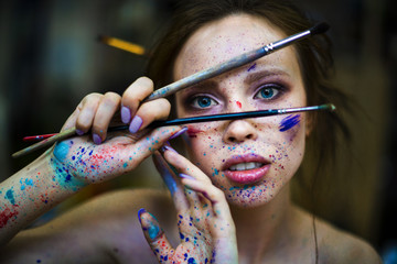 portrait of a woman artist with a drops of paints on the face and hands. looks at you through the brushes in the hand Wall mural