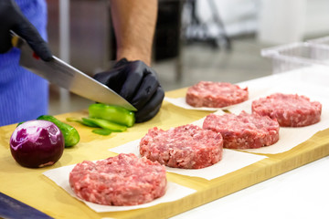 The chef prepares a Burger with beef, salad and vegetables.