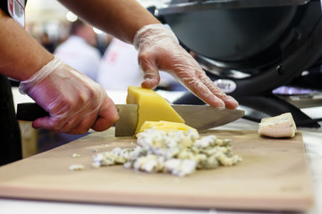 The chef cuts the cheese in the kitchen.