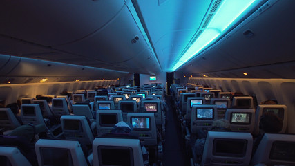 Interior passengers airplane with people on seats. Aircraft cabin with rows of seats. Passengers traveling by a modern commercial plane, inside of an airplane. Travel concept.