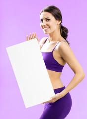 Woman in fitnesswear showing signboard, on rose