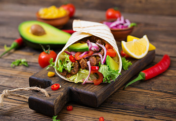 Mexican tacos with beef in tomato sauce and avocado salsa