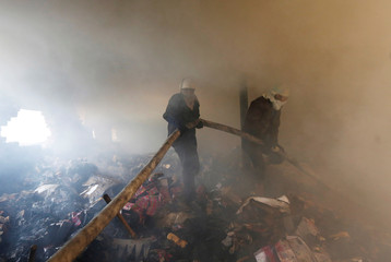 Rescue workers pull water pipe after fire broke out at footwear factory in New Delhi