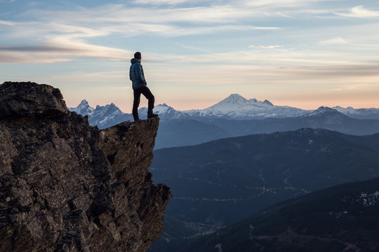Adventurous man on top of the mountain during a vibrant sunset. Taken on Cheam Peak, near Chilliwack, East of Vancouver, British Columbia, Canada.