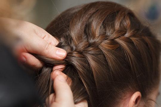 Female hands braid dark hair, close-up.