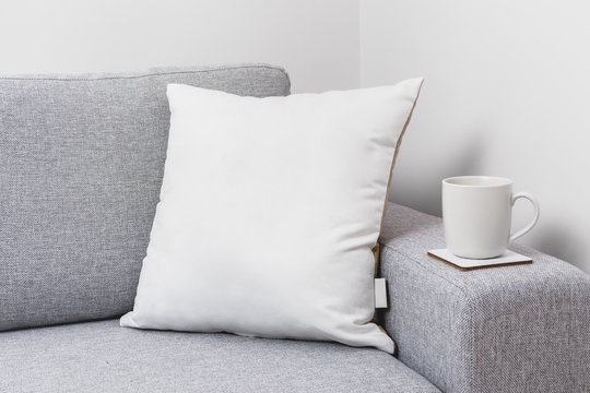 Blank white pillow on a couch with a tea cup.