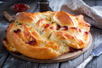 Cooked round cake made from yeast dough with dried tomatoes and cheese, horizontal