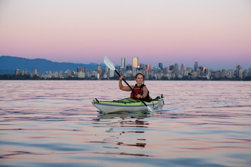 Middle Age Caucasian Woman Kayaking on a Sea Kayak during Sunset with City Skyline in Background. Taken in Vancouver, BC, Canada.