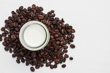 Coffee beans and milk in glass on white background